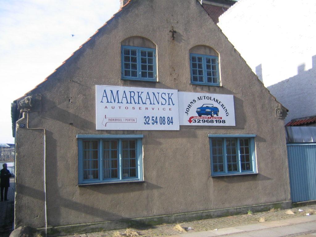 """Det gamle autoværksted. På skiltet """"Amarkansk autoservice"""" Johns autolakering. 32540884. Gammel murstensbygning i to plan. Før det blev til koncertsal til klassisk musik."""