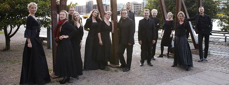 Kammerkor. Mogens Dahls kammerkor poserende i sort tøj ved Island Brygge. 13 personer i sort tøj. sangere, musikere og komponister