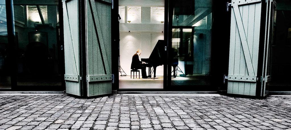 Koncertsalen nu. indblik ude fra gården. portene er åbne ind til en tidligere stal, hvor der nu sidder en mand og spiller på piano.